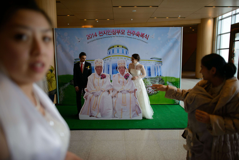 ". A newly-wed couple pose for photos with a cutout of church founder Sun Myung Moon following a mass wedding event held by the Unification Church in Gapyeong on February 12, 2014. Unification Church members forming 2500 couples from 52 countries were married in a mass wedding in South Korea -- only the second such event since the death of their ""messiah\"" and controversial church founder Sun Myung Moon. (ED JONES/AFP/Getty Images)"