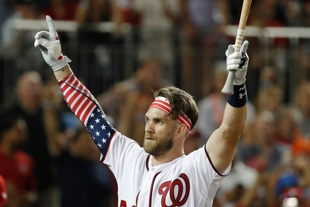 . Washington Nationals Bryce Harper (34) signals to the crowd as he walks back to the dugout during the MLB Home Run Derby, at Nationals Park, Monday, July 16, 2018 in Washington. The 89th MLB baseball All-Star Game will be played Tuesday. (AP Photo/Alex Brandon)