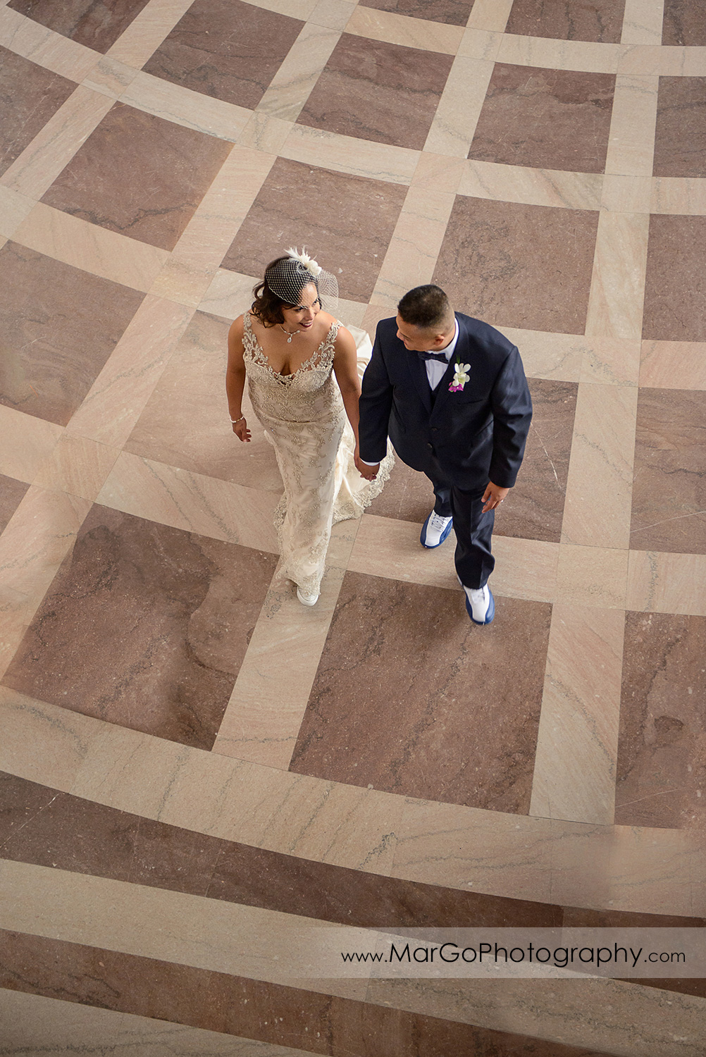 bride and groom walking together at San Francisco City Hall