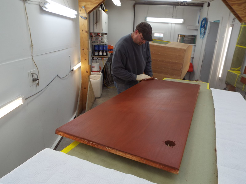 Wiping the excess stain on the desk top.
