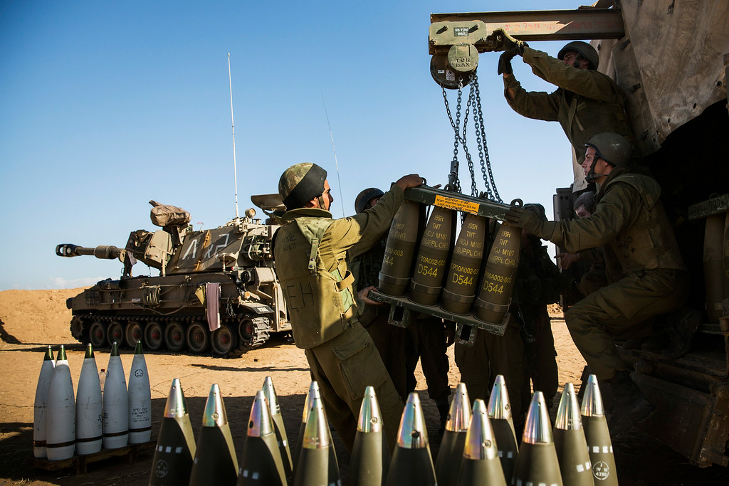 """. Israeli soldiers receive a new crate of artillery shells for firing into Gaza on July 17, 2014 near Sderot, Israel. As the Israeli operation \""""Protective Edge\"""" enters its tenth day, the body count in Gaza has reach over 200 people. One Israeli has been killed in a Mortar attack.  (Photo by Andrew Burton/Getty Images)"""