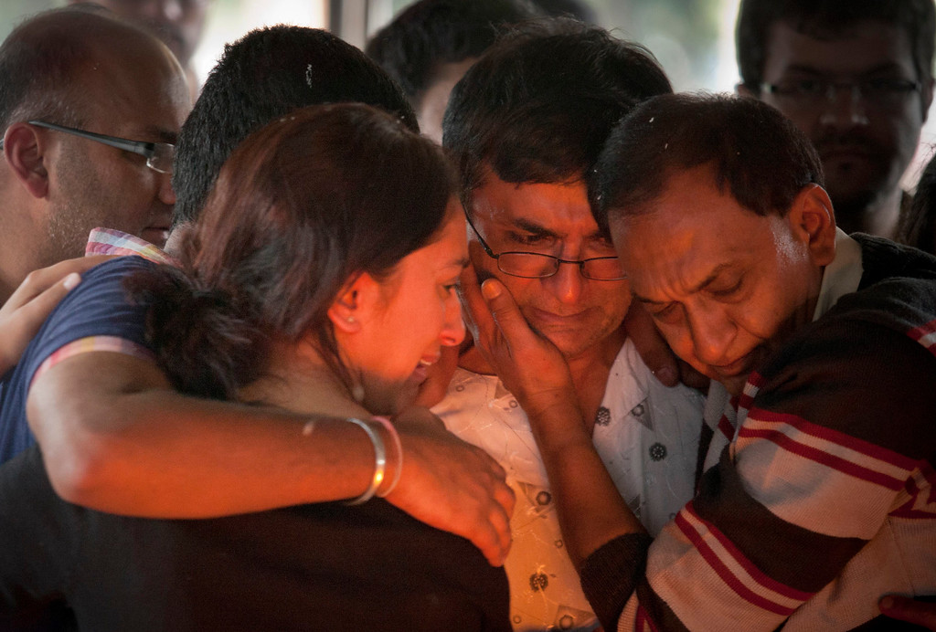 . Ramesh Vaya, center, is comforted by family members after lighting the funeral pyre for his wife Malti, who was shot dead in the attack on the Westgate Mall, at her funeral at the Hindu Crematorium in Nairobi, Kenya Tuesday, Sept. 24, 2013. Ramesh and his brother both lost their wives in the attack. Kenyan President Uhuru Kenyatta says security forces have finally defeated a small group of terrorists after four days of fighting at the Nairobi mall. (AP Photo/Kate Holt)