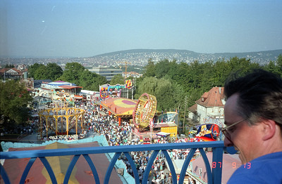 View of a carnival from top of some ride.  That is Zurich city in the background.