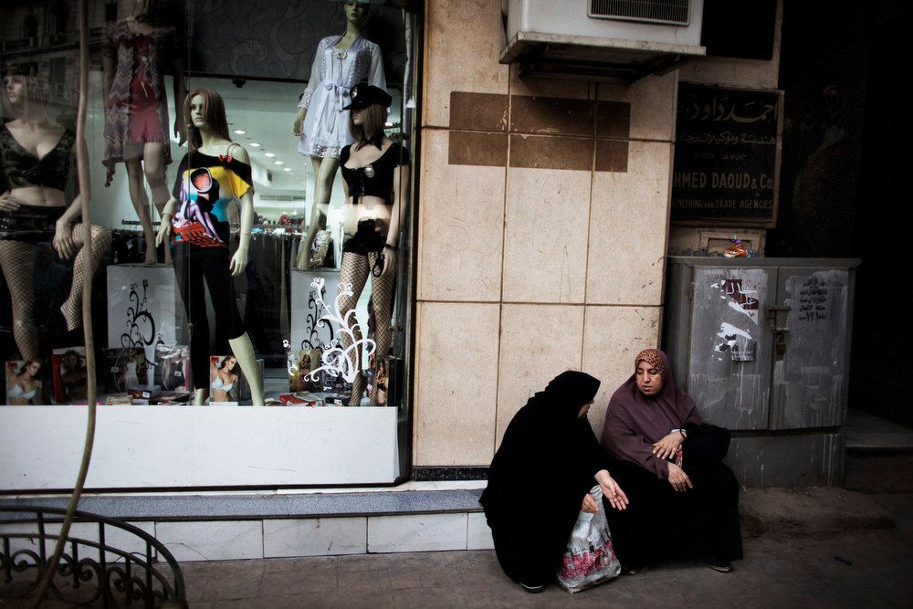 Description of . Egyptian women in traditional Islamic garb sit next to a shop displaying western clothes in a Cairo shopping district on May 26, 2012.  Final votes were still being counted, but unofficial results of Egypt's landmark presidential elections suggested that the top two vote-getters out of 12 candidates were the Muslim Brotherhood's Mohammed Mursi and Ahmed Shafiq, a former prime minister under Hosni Mubarak.   MARCO LONGARI/AFP/Getty Images