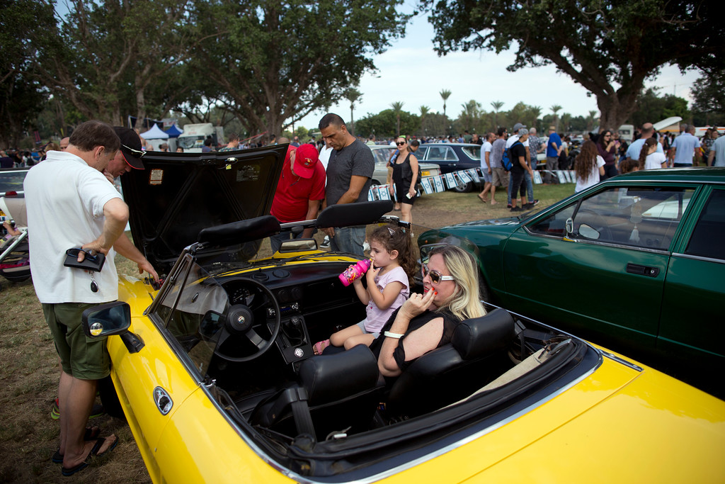 ". People look at antique cars during the 31st annual ""Five Club\"" collectors car meeting in Ramat Gan, Israel, Friday, Oct. 6, 2017. Each weekend, at Israeli gas stations and parking lots and parks, car collectors gather with their beauties _ and take a step back in time (AP Photo/Oded Balilty)"