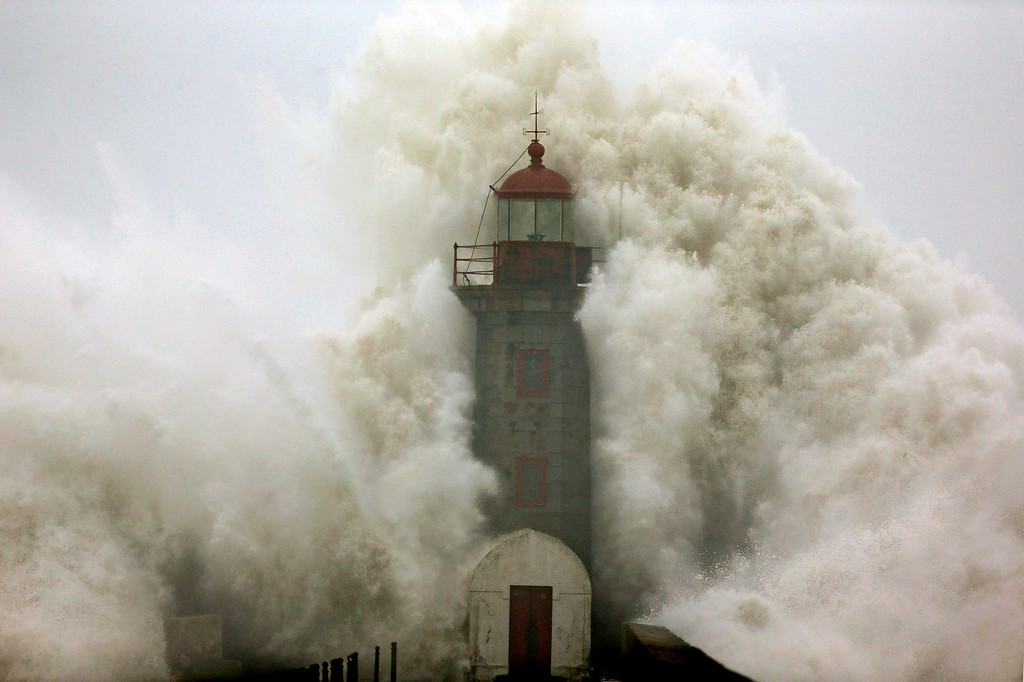 . A large wave strikes a lighthouse at the mouth of the River Douro, Porto, Portugal, 06 January 2014. The wave damaged some cars, as well as causing minor injuries to locals.  EPA/ESTELA SILVA