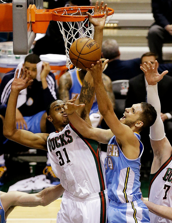. Denver Nuggets\' Evan Fournier, right, shoots against Milwaukee Bucks\' John Henson(31) during the first half of an NBA basketball game, Monday, April 15, 2013, in Milwaukee. (AP Photo/Jeffrey Phelps)