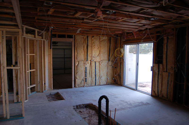 The kitchen, looking toward the door to the side yard, and the door into the garage. The plumbing for the island is in the foreground.