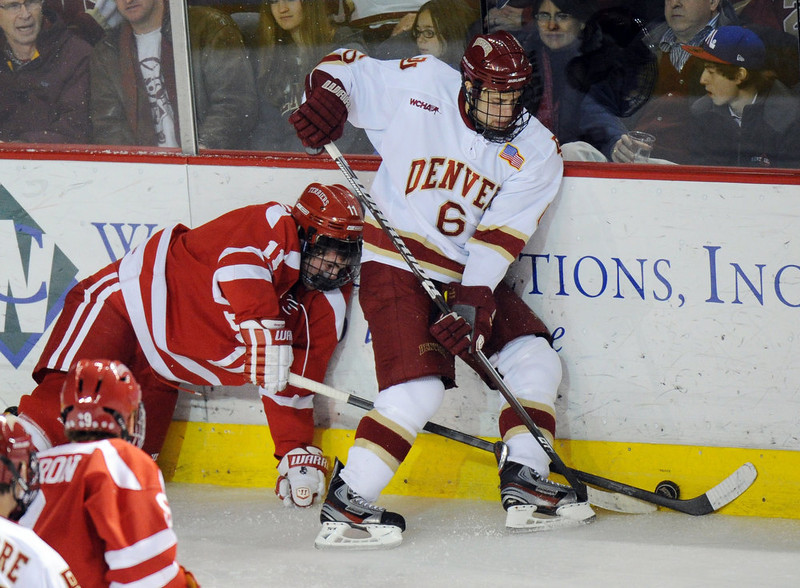 . Boston University\'s Mike Moran, left, and University of Denver\'s Dakota Mermis fight for the control of puck in the 2nd period of the game at Magness Arena in Denver, Colo. on Saturday, December 29, 2012. Hyoung Chang, The Denver Post