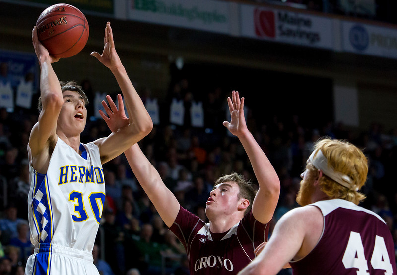 BANGOR, Maine -- 02/22/2017 -- Hermon's Isaac Varney (left) puts up a shot past Orono's Connor Robertson (center) and Orono's Jackson Coutts during their Class B boys basketball semifinal game at the Cross Insurance Center in Bangor Wednesday. Ashley L. Conti | BDN