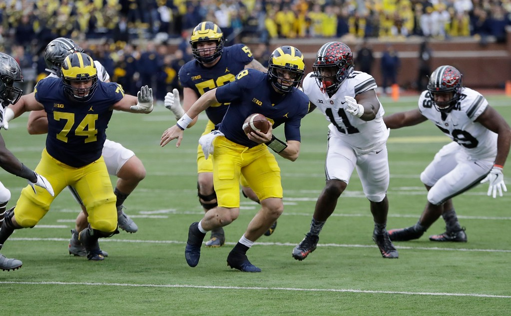 . Michigan quarterback John O\'Korn (8) scrambles during the second half of an NCAA college football game against Ohio State, Saturday, Nov. 25, 2017, in Ann Arbor, Mich. (AP Photo/Duane Burleson)