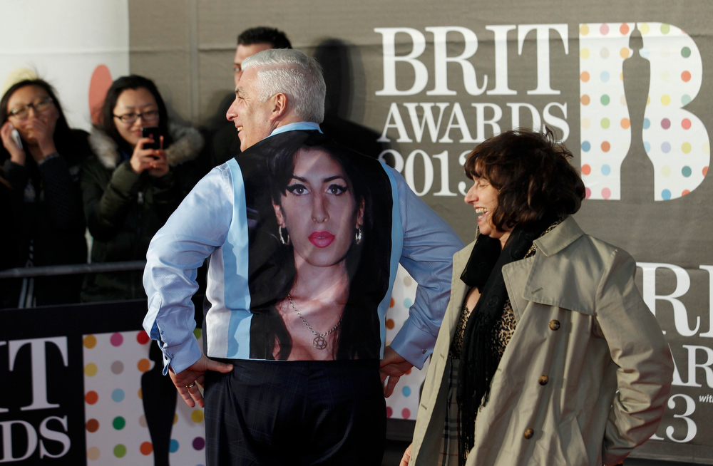 Description of . Mitch and Janis Winehouse, the father and mother of the late singer Amy Winehouse, laugh as they arrive for the BRIT Awards at the O2 Arena in London February 20, 2013. Mitch has taken off his jacket to display a picture of Amy on his waistcoat. Last month eyebrows were raised when Amy Winehouse was nominated in the British female solo category some 18 months after her death for a chart-topping album of unreleased songs and demos called