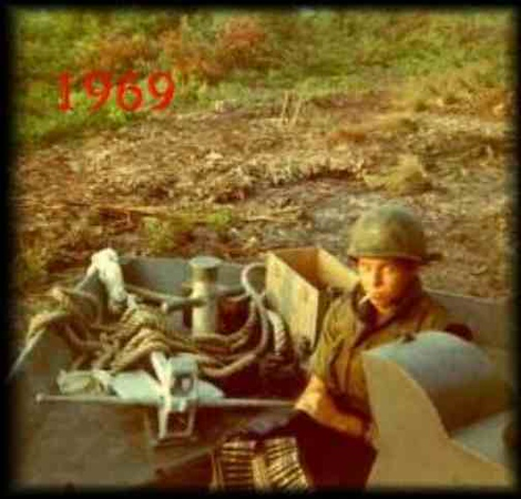 . Submitted <br> Joe Muharsky in Gun tub with boat beached in canal. M60 machine gun.