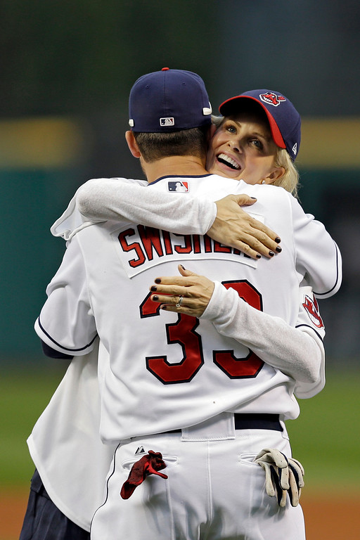 . Actress Monica Potter hugs Cleveland Indians\' Nick Swisher after a ceremonial pitch before a baseball game against the Houston Astros Thursday, Sept. 19, 2013, in Cleveland. (AP Photo/Mark Duncan)