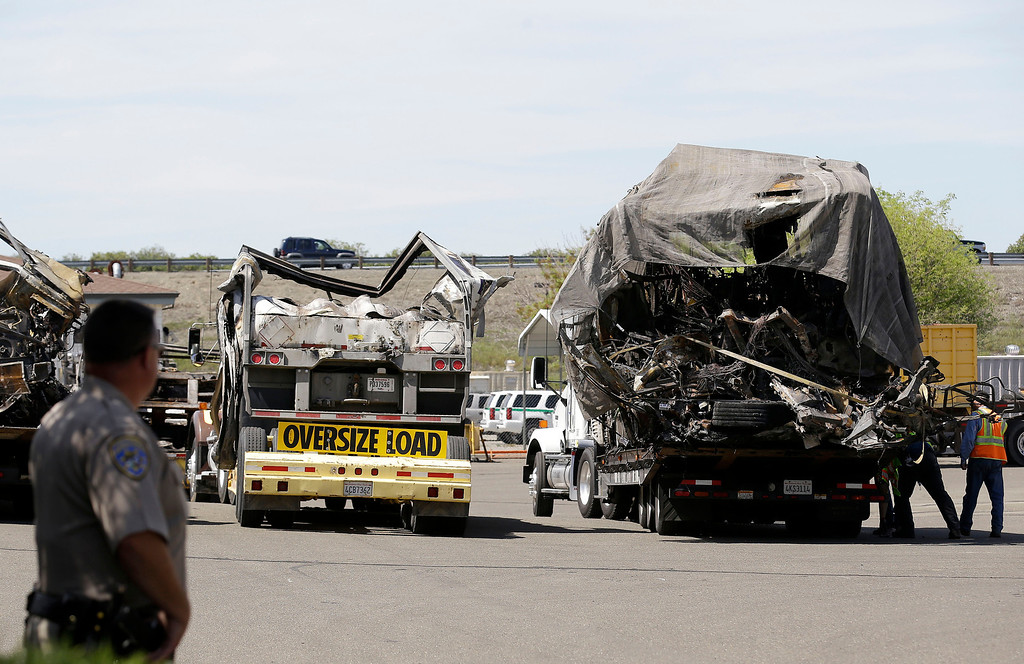 . A California Highway Patrol officer stands at a gate as the demolished remains of a FedEx truck sit in a CalTrans maintenance station in Willows, Calif., Friday, April 11, 2014. At least ten people were killed and dozens injured in the fiery crash on Thursday, April 10, between a FedEx truck and a bus carrying high school students on a visit to a Northern California college. (AP Photo/Jeff Chiu)