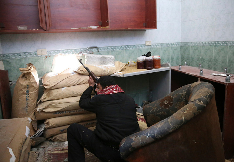 . A Free Syrian Army fighter takes position inside a house during clashes with forces loyal to Syria\'s President Bashar al-Assad in the Arabeen neigbourhood of Damascus, February 12, 2013. REUTERS/Mohammed Abdullah