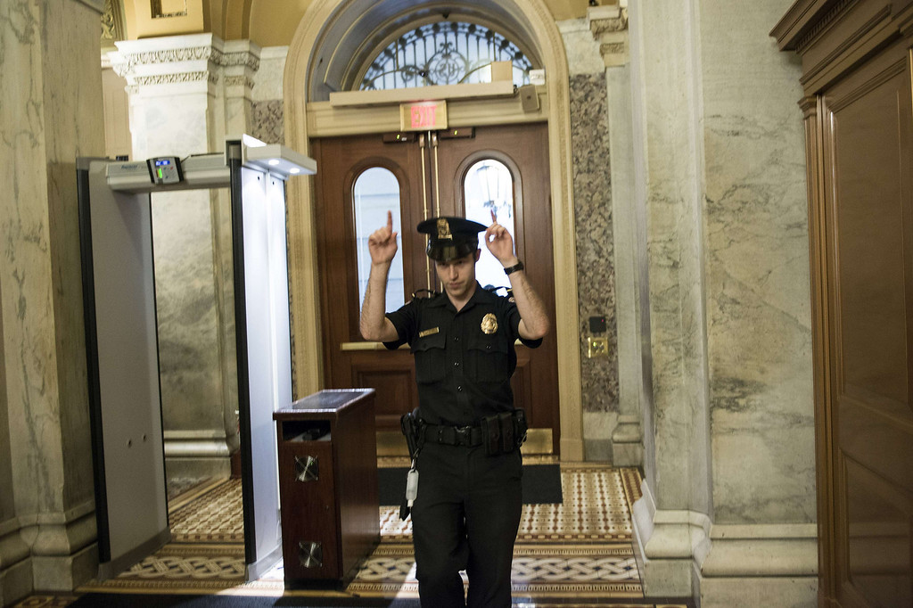 """. A Capitol Police Officer directs people away from a door on Capitol Hill October 3, 2013 in Washington, DC. The US Capitol was placed on security lockdown Thursday after shots were fired outside the complex, senators said. \""""Shots fired outside the Capitol. We are in temporary lock down,\"""" Senator Claire McCaskill said on Twitter. Police were seen running within the Capitol building and outside as vehicles swarmed to the scene. AFP PHOTO/Brendan  SMIALOWSKI/AFP/Getty Images"""