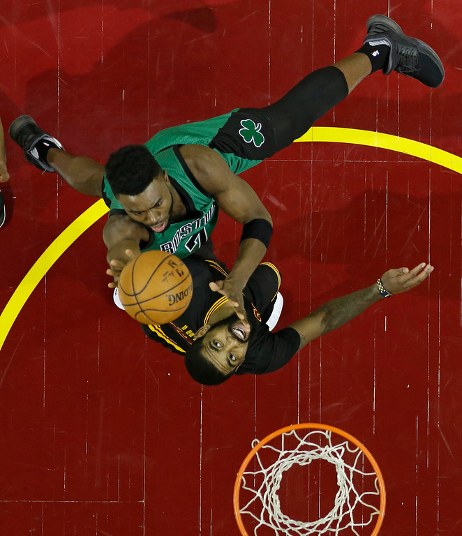 . Boston Celtics\' Jaylen Brown, top, shoots over Cleveland Cavaliers\' Kyrie Irving in the first half of an NBA basketball game, Thursday, Dec. 29, 2016, in Cleveland. (AP Photo/Tony Dejak)