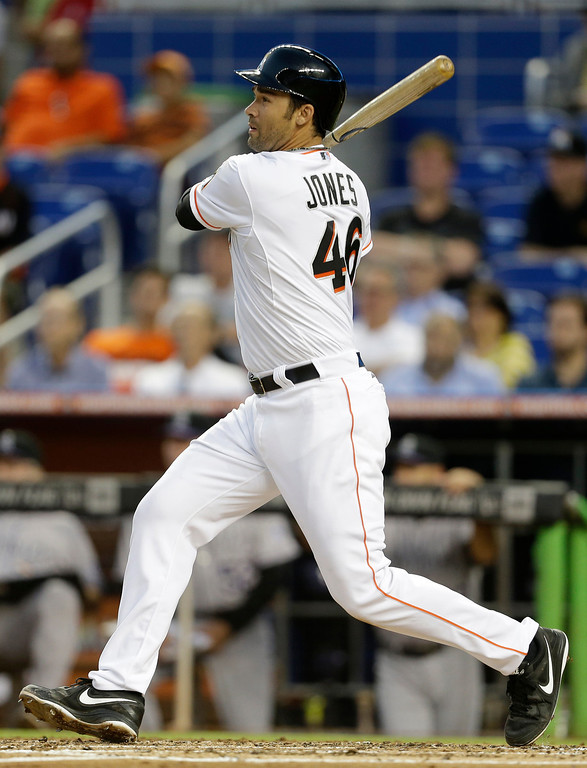 . Miami Marlins\' Garrett Jones watches after hitting an RBI-single to score Derek Dietrich in the first inning of a baseball game against the Colorado Rockies, Wednesday, April 2, 2014, in Miami. (AP Photo/Lynne Sladky)