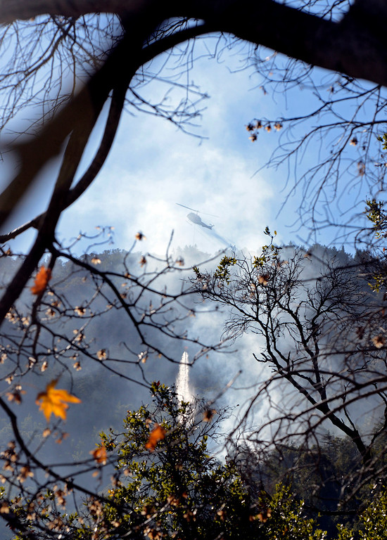 . A helicopter makes a water drop on Pfeiffer Ridge above Fernwood as firefighters near the end of their battle with the Pfeiffer Ridge Fire in Big Sur, Calif. on Friday December 20, 2013. (Photo David Royal/ Monterey County Herald)