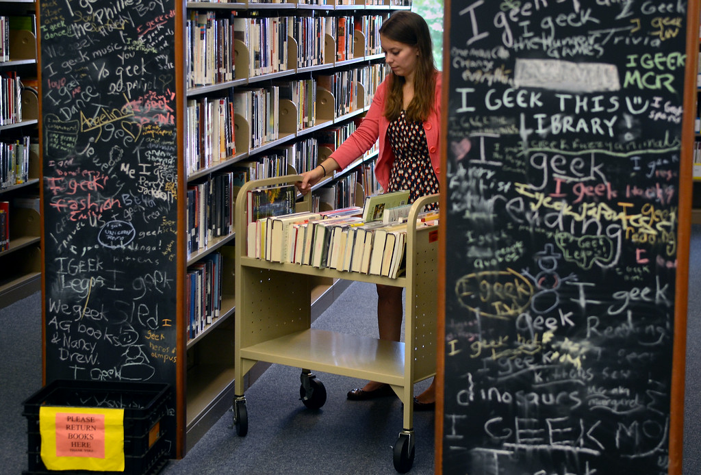 . Springfield Township Library Electronic Resources Librarian shelves books at the library on Thursday August 7,2014. Photo by Mark C Psoras/The Reporter