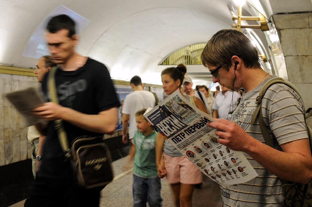 . Ukrainians read newspapers at a metro station, in Kiev, Ukraine, Monday, May 26, 2014. Early returns on Monday suggested candy tycoon Petro Poroshenko was ahead in the first round of balloting of the Ukraine presidential election. (AP Photo/Evgeniy Maloletka)