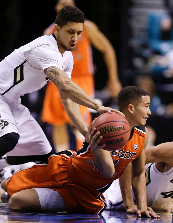 . Colorado\'s Askia Booker, left, tries to strip the ball as Oregon State\'s Challe Barton looks to pass in the second half during a Pac-12 tournament NCAA college basketball game on Wednesday, March 13, 2013, in Las Vegas. Colorado won 74-68. (AP Photo/Julie Jacobson)