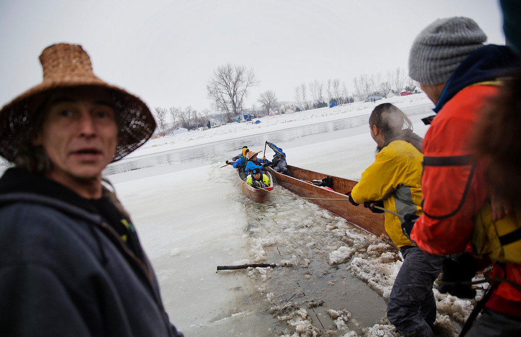 . In this Thursday, Dec. 1, 2016 photo, a canoe carrying members of the Colville Native American tribe are pulled into shore upon arriving at the Oceti Sakowin camp where people have gathered to protest the Dakota Access oil pipeline in Cannon Ball, N.D. They traveled from Montana with fellow tribal members on canoe for 10 days down the Missouri river to reach the camp. (AP Photo/David Goldman)
