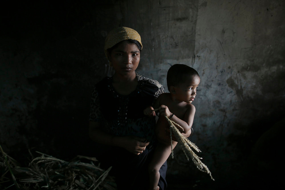 . Hla Hla May, a Rohingya Muslim woman displaced by violence, holds her one year old daughter Roshan at a former rubber factory that now serves as their shelter, near Sittwe April 29, 2013. Myanmar must urgently address the plight of Muslims displaced by sectarian bloodshed in western Rakhine State and double the number of security forces to control the still-volatile region, an independent commission said on Monday.   REUTERS/Damir Sagolj