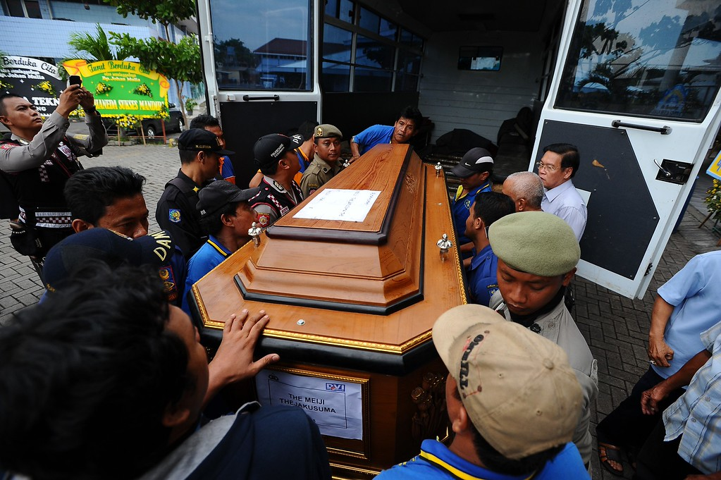 . Workers carry the coffin of Meiji Thejakusuma, victim of AirAsia flight QZ8501 crash at Adi Yasa funeral home on January 3, 2015 in Surabaya, Indonesia. A massive recovery operation is underway in waters off Borneo to recover bodies and debris from the missing AirAsia plane. AirAsia announced that flight QZ8501 from Surabaya to Singapore, with 162 people on board, lost contact with air traffic control at 07:24 a.m. local time on December 28.  (Photo by Robertus Pudyanto/Getty Images)