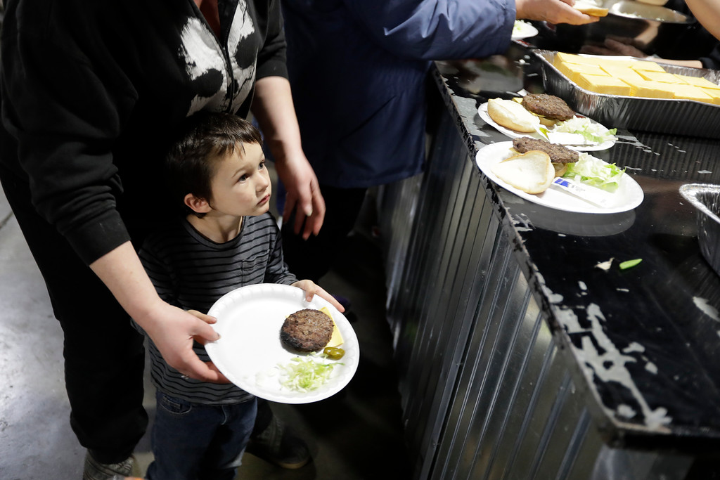 . Jace Duran, 4, of Oroville, Calif., at left, waits in line for a meal at a shelter for evacuees from cities surrounding the Oroville Dam, Monday, Feb. 13, 2017, in Chico, Calif. The thousands of people who were ordered to leave their homes after a damaged California spillway threatened to unleash a 30-foot wall of water may not be able to return until significant erosion is repaired, authorities said Monday. (AP Photo/Marcio Jose Sanchez)