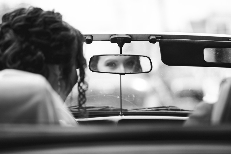 The brides eyes in the rear view mirror of the convertible.