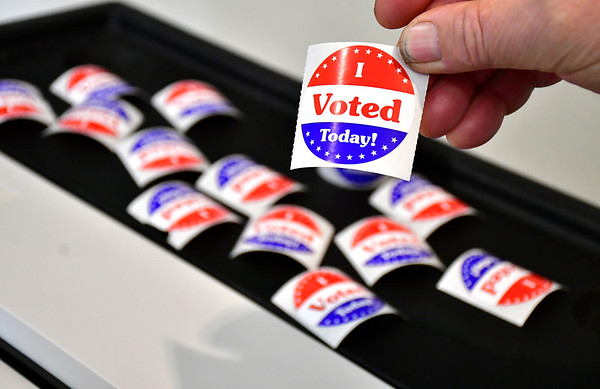 4/30/2019 Mike Orazzi   Staff Joe Szczepanski holds stickers for voters at the Plainville Fire Station during Tuesday's budget vote.