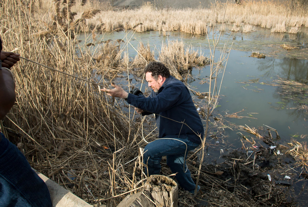 . Beduareo Marquez climbs up the pond embankment where he retrieved a shoe from the crash site that six teens died on Park Ave. in Warren, Ohio on Sunday, March 10, 2013. (AP Photo/Scott R. Galvin)