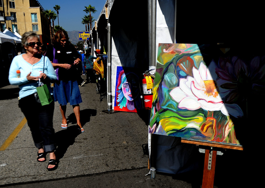 . Locals walk past over 30 booths during the 8th Annual Pasadena ARTWalk along El Molino Avenue between Colorado Boulevard and Green Street in Pasadena, Calif., on Saturday, Oct. 12, 2013. The ArtWalk features over 30 participating artists, art sales, gallery walks, musical performances and other activities.   (Keith Birmingham Pasadena Star-News)