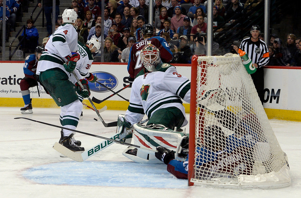 . Goalie Charlie Coyle (3) of the Minnesota Wild looks at Nathan MacKinnon (29) of the Colorado Avalanche as he slides into the net during the third period of action. The Colorado Avalanche hosted the Minnesota Wild for the first playoff game at the Pepsi Center on Thursday, April 17, 2014. (Photo by John Leyba/The Denver Post)