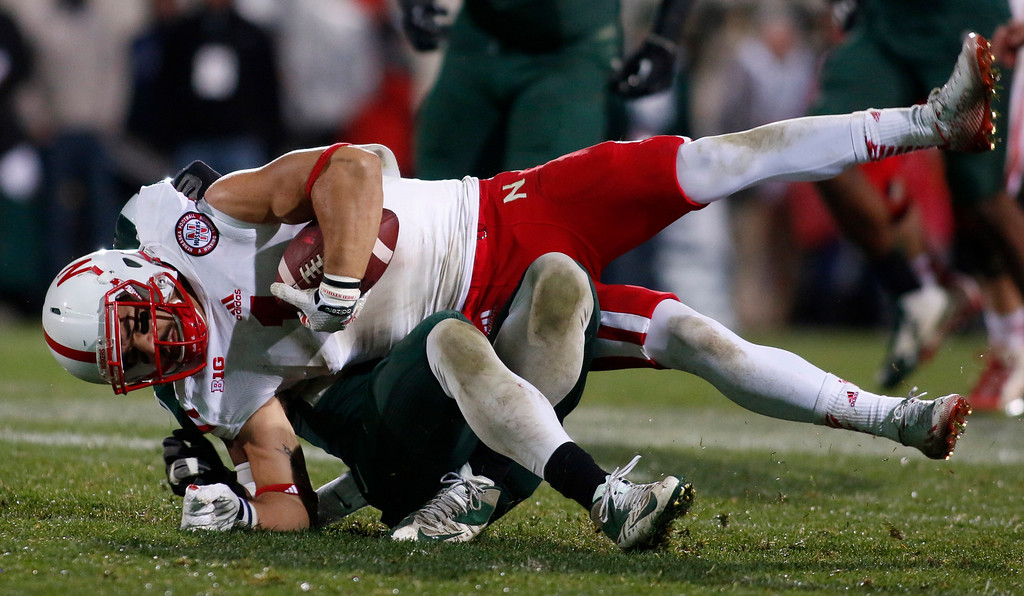 . Nebraska receiver Jordan Westerkamp, top, is tackled by Michigan State\'s Kurtis Drummond during the fourth quarter of an NCAA college football game, Saturday, Oct. 4, 2014, in East Lansing, Mich. Michigan State won 27-22. (AP Photo/Al Goldis)