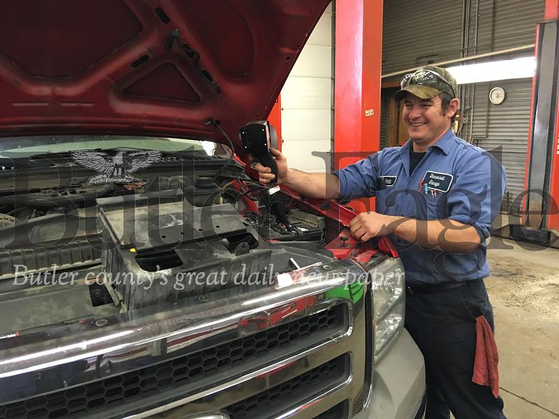 Dinnerbell Garage mechanic Fred Pfeifer checks a truck battery. Steve Ferris/butler eagle
