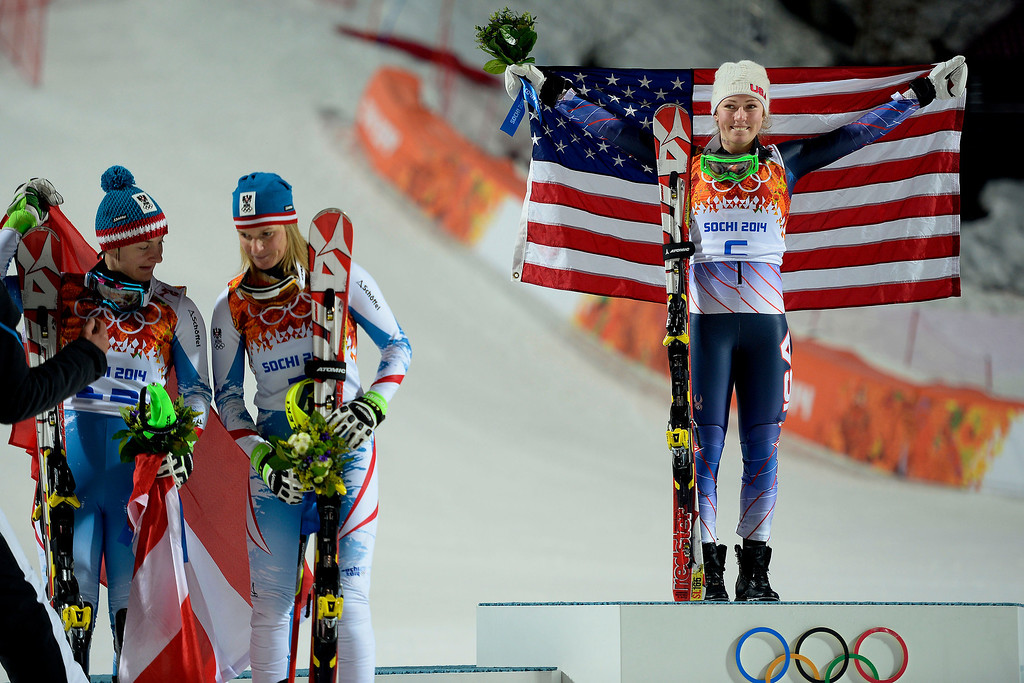 . Gold medalist American Mikaela Shiffrin raises her flag as silver Marlies Schild (center) and bronze medalist Kathrin Zettel (both of Austria) stand nearby after ladies\' slalom run 2. Sochi 2014 Winter Olympics on Friday, February 21, 2014 at Rosa Khutor Alpine Center. (Photo by AAron Ontiveroz/ The Denver Post)