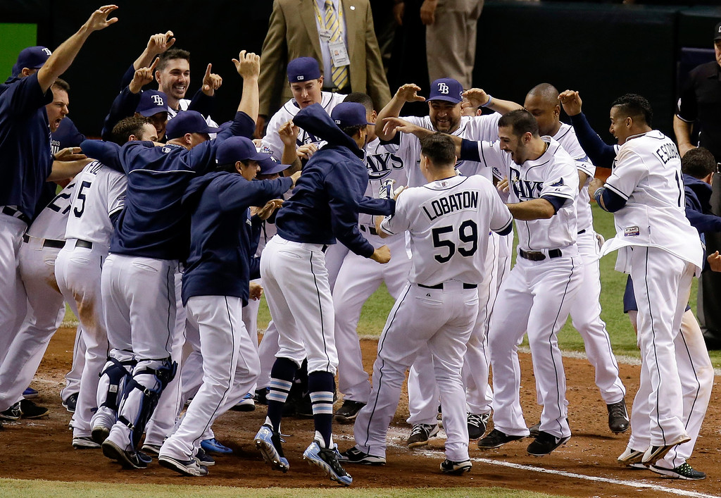 . Tampa Bay Rays\' Jose Lobaton (59) is surrounded by teammates as he heads to home plate after hitting a walk off home run in the ninth inning against the Boston Red Sox in Game 3 of an American League baseball division series in St. Petersburg, Fla., Monday, Oct. 7, 2013. Tampa Bay Rays won 5-4. (AP Photo/John Raoux)