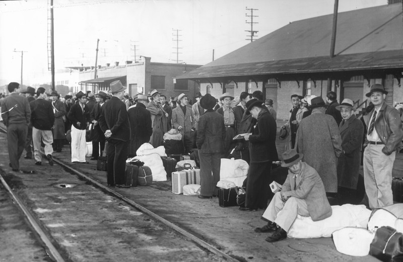 """""""Old Santa Fe Railroad station hundreds of Japanese yesterday boarded a 13-coach train bound for Inyo, where they will transfer to trucks"""" -- caption on photograph"""