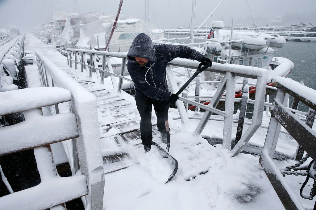 . Kevin Hancock clears snow from a dock at the Boston Harbor Shipyard and Marina in Boston, Tuesday, March 13, 2018. Boston finds itself in the bullseye of the third nor\'easter in two weeks, with forecasters warning of up to 18 inches of snow and 2 feet or more to the south. (AP Photo/Michael Dwyer)