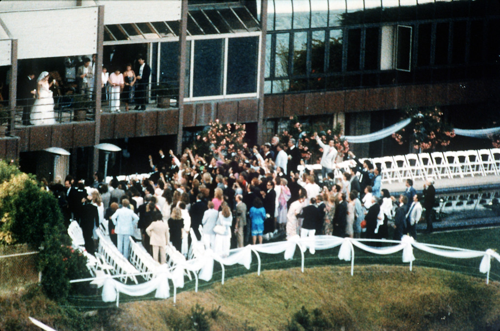 . U.S. pop singer Madonna and U.S. actor Sean Penn, top left on balcony, accept a toast by their guests at their wedding in Malibu, CA, Aug. 17, 1985. (AP Photo/Doug Pizac)