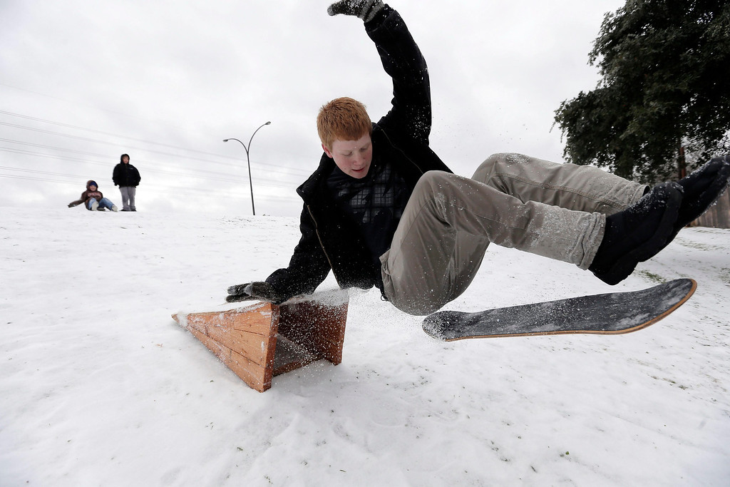 . Matthew Eller, 15, catches air after sliding down a hill and jumping a ramp in Arlington, Texas, USA, 06 December 2013. A large ice storm causing travel problems and power outages moved through the Dallas, Texas area and across the midwest.  EPA/BRANDON WADE