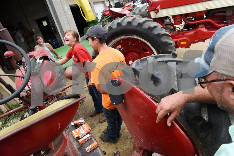 Harold Aughton/Butler Eagle: Robyn Freund, 17, a junior at Butler High School, shares a laugh with co-worker Brady Stewart as they work together to change the spark plugs in a 1950 Farmall tractor as Emily and Guy supervise.