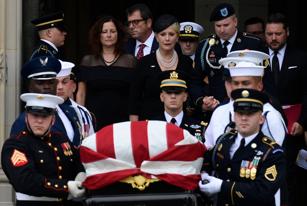 . Cindy McCain, center, widow of Sen. John McCain, R-Ariz., escorted by her son Jimmy McCain and other family members, follows his casket as it is carried out of Washington National Cathedral in Washington, Saturday, Sept. 1, 2018, following a memorial service. McCain died Aug. 25 from brain cancer at age 81. (AP Photo/Susan Walsh)