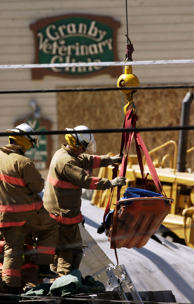 . Firefighters move the body of  Marvin Heemeyer by using a crane from the bulldozer at Gambles store, Granby on June 5, 2004. (HYOUNG CHANG/ THE DENVER POST)