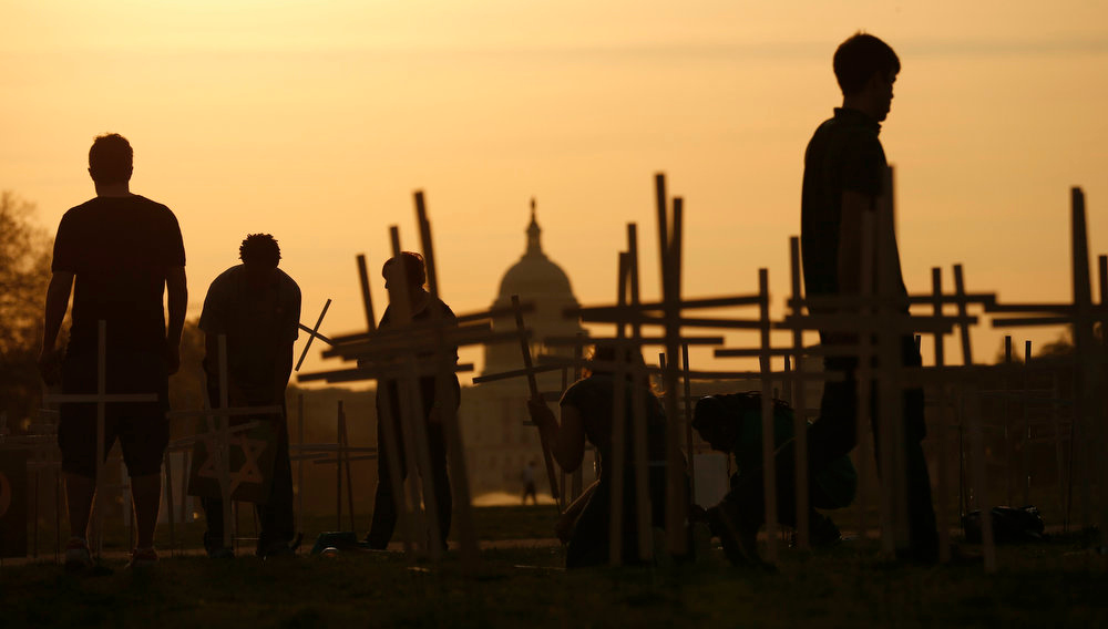 "Description of . The sun rises above the U.S. Capitol as volunteers place crosses symbolizing grave markers on the National Mall in Washington on April 11, 2013. The PICO National Network\'s Lifelines to Healing and Sojourners are holding a 24-hour vigil featuring a gathering of Newtown clergy and 3,300 grave markers to ""remind Congress action is needed on gun violence prevention.\"" The number 3,300 represents the supposed number of people who have died as a result of gun violence since the tragedy in Newtown, Connecticut.   REUTERS/Kevin Lamarque"
