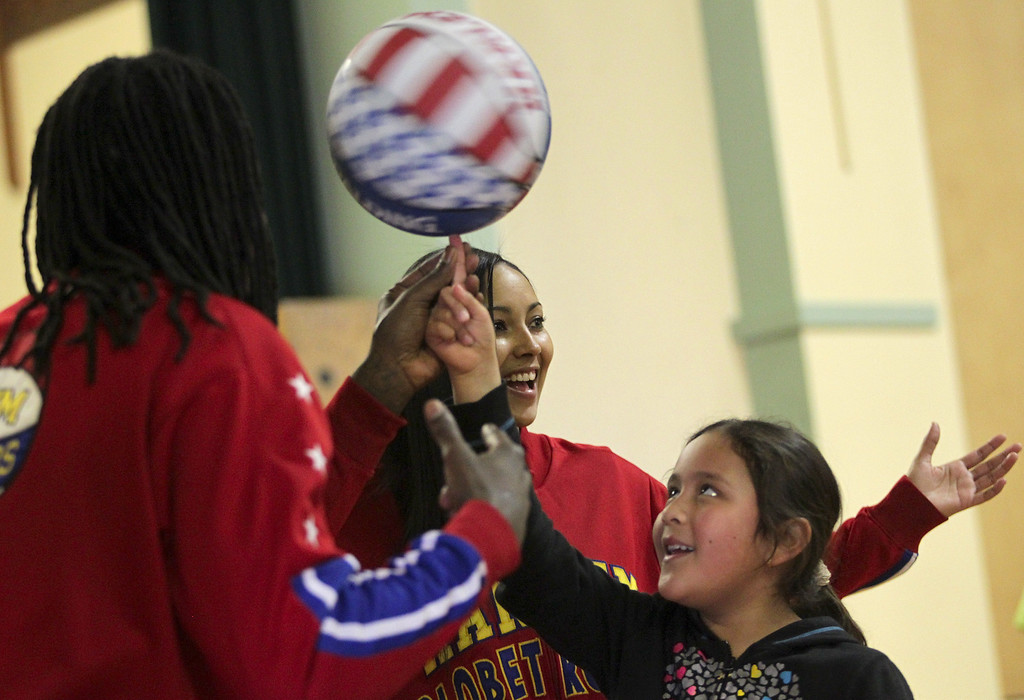 . Harlem Globetrotters� Slick Willie Shaw, from left, and rookie teammate and Oakland native Tammy �T-Time� Brawner help Laurel Elementary student Alexandra Perez Escobar, 8, spin a basketball during a visit in Oakland, Calif., on Wednesday, Jan. 16, 2013. (Anda Chu/Staff)