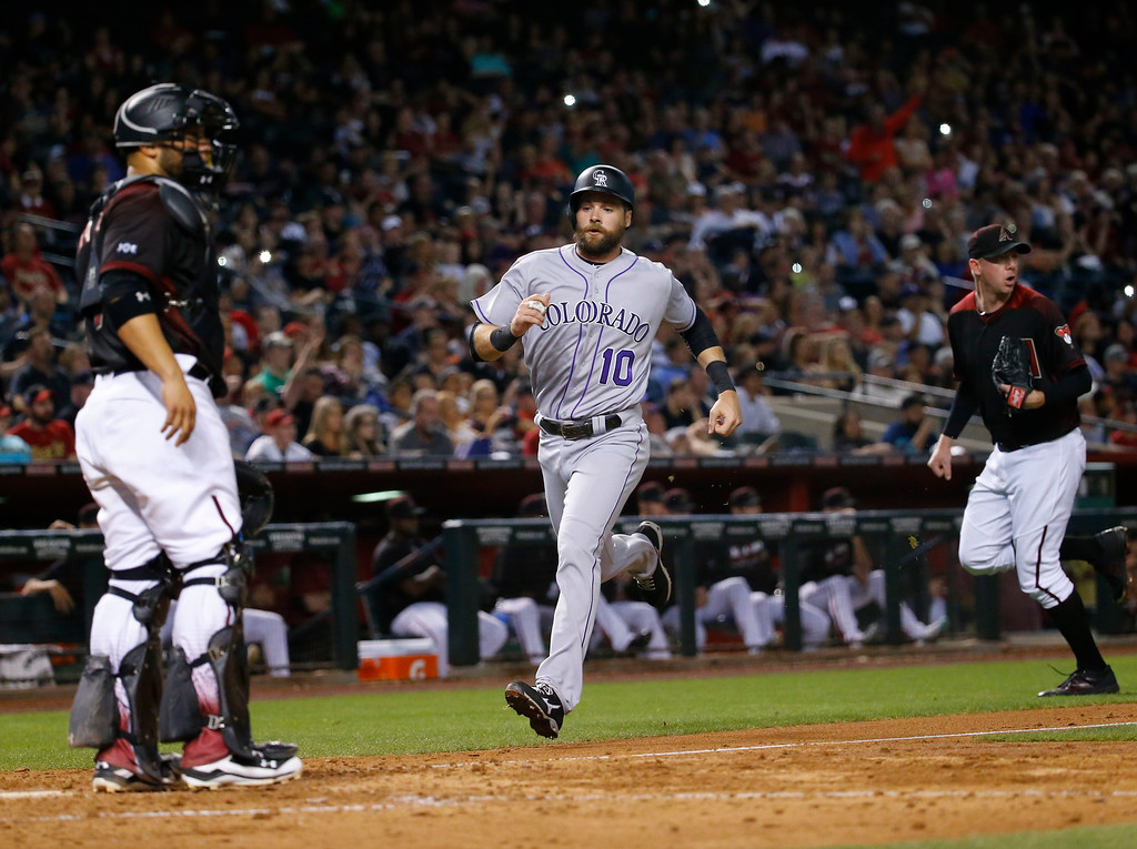. Colorado Rockies\' Ben Paulsen (10) scores on a two-RBI triple by Trevor Story during the ninth inning of a baseball game against the Arizona Diamondbacks, Saturday, April 30, 2016, in Phoenix. (AP Photo/Matt York)